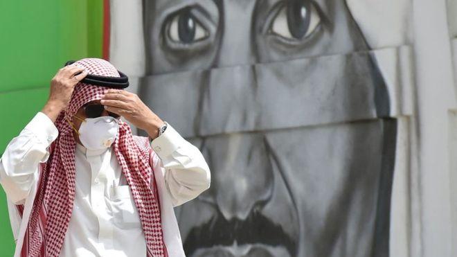 Seorang pria mengnakan masker melintas di depan foto Raja Salman. (Foto: Saudileaks)
