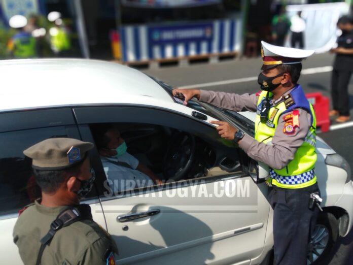 Petugas kepolisian di Pos PAM Penyekatan Prambanan terlihat sedang menempelkan stiker di setiap mobil yang usai diperiksa kelengkapan dokumennya. Foto: Gaga Sallo